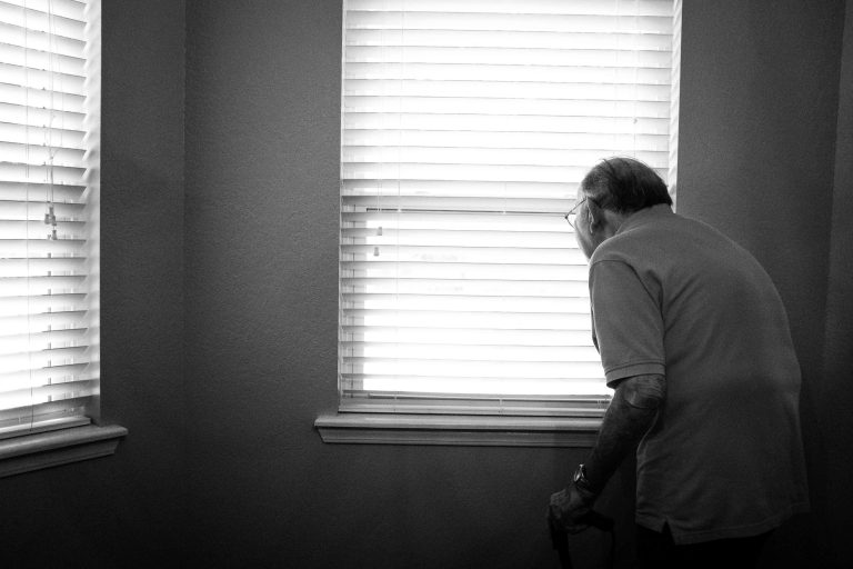 Man looking out window for restraints blog.
