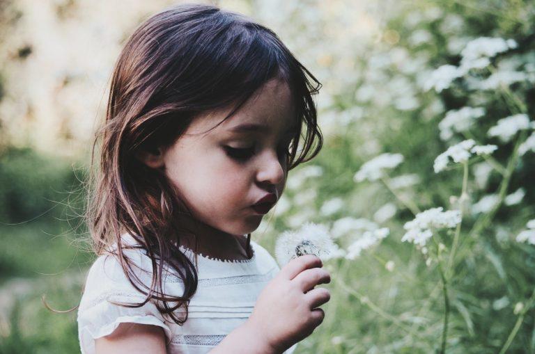 Girl with flower for child safe blog.