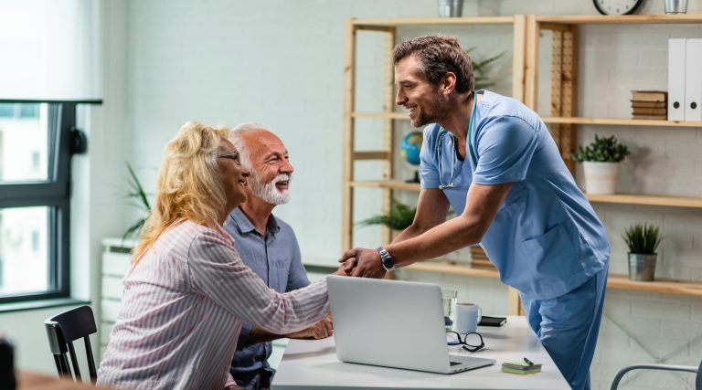 Happy doctor greeting senior couple and shaking hands with a woman at his office.