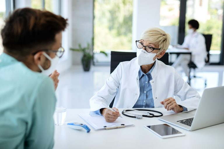 Mature doctor wearing face mask while talking to a patient at medical clinic for the RACGP standards