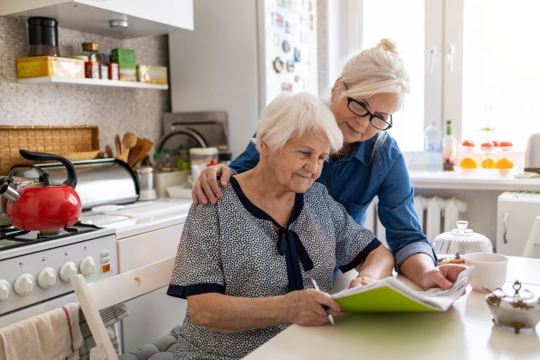 Mature woman helping older woman experiencing elder financial abuse